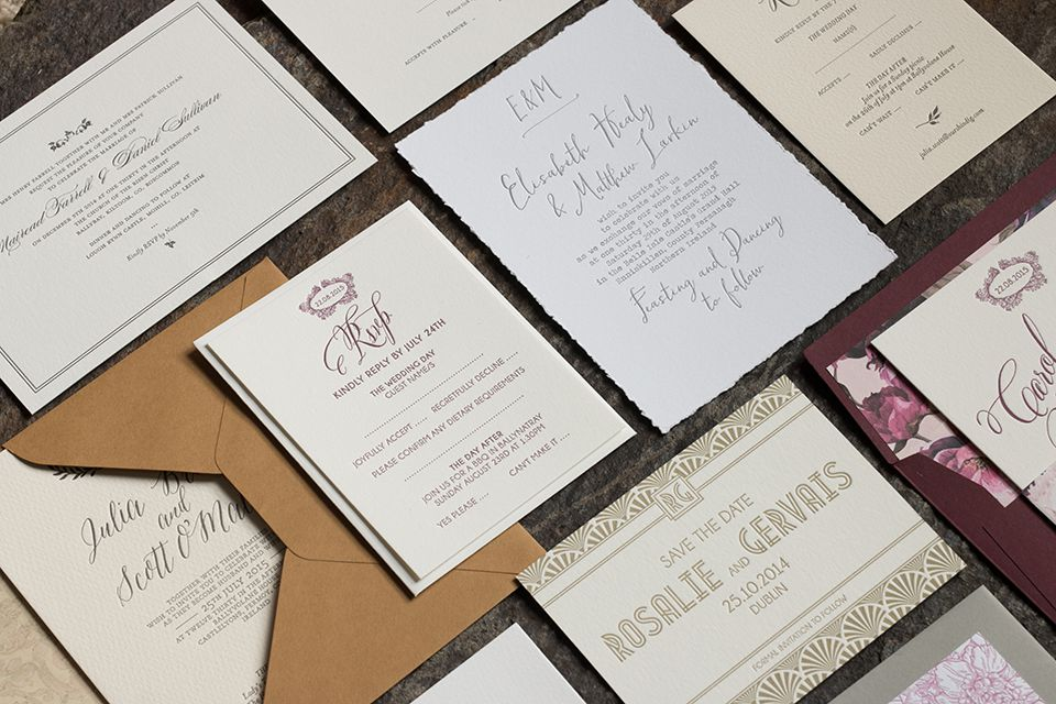 Collection of letterpress wedding invitations in various inks resting on a flat surface