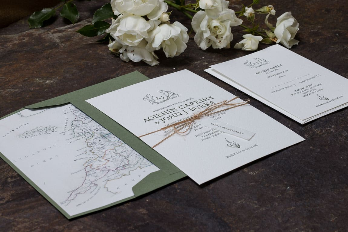 Wedding Invitation with name tag tied around it resting on green envelope with an envelope liner showing County Clare in Ireland