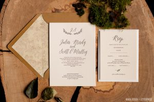 Wedding Invitation and RSVP resting on log